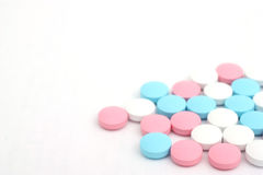 Pillole sui precedenti bianchi Immagine Stock