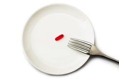 Pillole sul piatto bianco con la forcella Pillola invece di alimento Immagini Stock Libere da Diritti