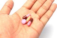Pillole sulla mano dell'uomo Fotografia Stock