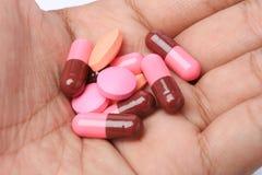 Pillole sulla mano dell'uomo Fotografie Stock