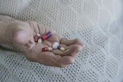 Pillole sulla palma di una donna senior immagini stock libere da diritti