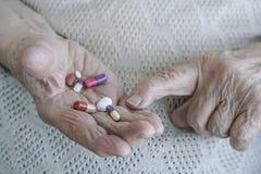 Pillole sulla palma di una donna senior fotografia stock