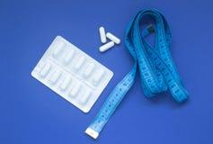 Pillole in una bolla ed in un nastro di misurazione su un fondo blu fotografia stock
