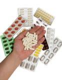Pillole in una mano ed in borse delle droghe Fotografie Stock