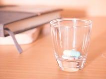 Pillole in una tazza di vetro con la sfuocatura del taccuino per fondo Fotografia Stock Libera da Diritti