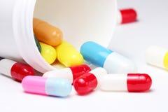 Pillole variopinte con la latta Fotografie Stock Libere da Diritti