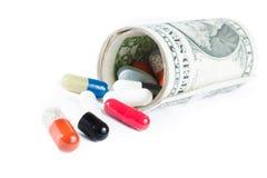 Pillole variopinte davanti ai dollari acciambellati su fondo bianco Fotografia Stock
