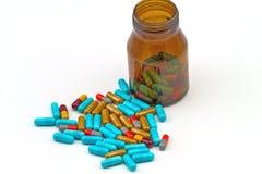 Pillole variopinte e compresse della bottiglia su fondo bianco fotografia stock libera da diritti