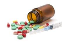 Pillole variopinte, una bottiglia e una siringa Fotografia Stock Libera da Diritti