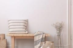 Pillow и укрывайте на деревянной скамье рядом с цветками в бежевом минимальном плоском интерьере Реальное фото стоковые изображения rf