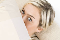 Pillow. Portrait of a pretty blond female wearing evening pink gown sitting on sofa with braids and arming a pillow Stock Image