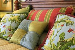 Pillow Assortment. Assortment of brightly colored pillows on mahagony bed with gold bedspread royalty free stock images