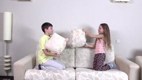 Pillow battle, slowmotion. Pillow battle, little girl and boy staged a pillow fight on a sofa in the living room, large beige sofa, girl with long hair, boy in stock video