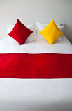 Pillow on bed. Red and yellow pillows on white bed Stock Images