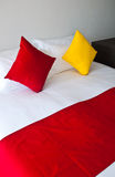 Pillow on bed. Red and yellow pillows on white bed Stock Photo
