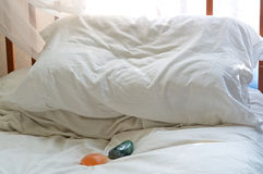 Pillow on bed with healing stones Royalty Free Stock Image