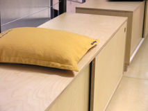 Pillow on a bench. Yellow decorational pillow on a modern plywood bench in an office Stock Photo
