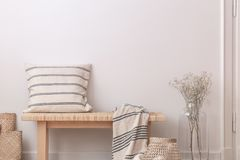 Pillow and blanket on wooden bench next to flowers in beige minimal flat interior. Real photo. Concept royalty free stock images