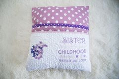 A pillow for book with a message. A pillow for book with the message: A sister is a little bit of childhood that can never be lost stock photography