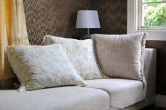 Pillow cushions On Sofa. Detail of modern living room with table lamp and pillow cushions on sofa Royalty Free Stock Image