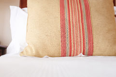 Pillow with elegant design on a wooden bed Royalty Free Stock Image