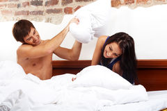 Pillow fight. Young happy couple having a pillow fight in a bed royalty free stock photo
