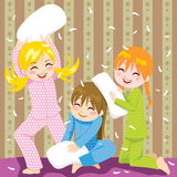 Pillow fight. Three young girls having fun doing pillow fight in a pajama party Stock Photos