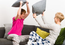Pillow fight. Happy lesbian couple have a pillow fight on the couch, horizon format stock photos