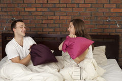 Pillow fight. Young couple having a pillow fight royalty free stock image