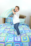 Pillow Fight. Happy five year old boy throwing pillow towards camera Royalty Free Stock Photography