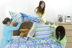 Pillow Fight. Three young teen girls having pillow fight at home