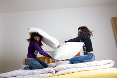 Pillow Fight. A view of two teenage girls having a pillow fight in their bedroom stock images