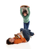 Pillow Fight. A laughing girls on the ground laughing while being whacked by another girl with a pillow.  Isolated on white Stock Photos