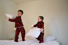 Pillow fight. Boys having a pillow fight while laughing on bed royalty free stock images