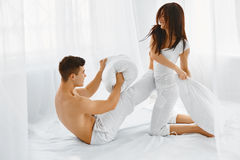Pillow Fight. Couple having fun. Pillow Fight. Young beautiful couple having fun on the bed in the bedroom in the morning royalty free stock image