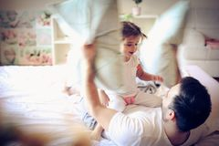 Pillow fight with daddy is fun. Little girl. royalty free stock images