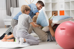 Pillow fight between father and children. Father having a pillow fight with his children in living room stock images