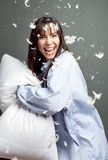 Pillow Fight with Happy Woman. Pillow fight with a happy smiling woman wearing a man's shirt, feathers in the air stock images