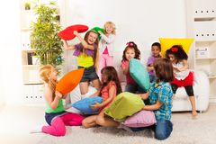 Pillow fight. Large group of kids, boys and girls playing in the living room hitting each other with colorful pillows stock images
