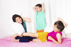Pillow fight. Mother and her two sons having a pillow fight in bedroom stock photos