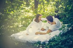 Pillow fight in nature. Couple have fun at morning in nature stock photography