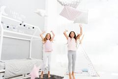 Pillow fight pajama party. Evening time for fun. Sleepover party ideas. Girls happy best friends or siblings in cute. Stylish pajamas with pillows sleepover stock image