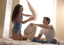 Pillow Fight. Portrait of happy loving couple having a pillow fight in bed stock images