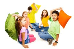 Pillow fight - ready, steady go... Happy five teen kids, Caucasian, black and Asian, boys and girls ready to start fighting with pillows, laughing and having Stock Images