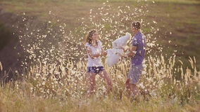 Pillow fight. Young couple are madly having fun. A woman is beating her pillow with a friend