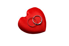Pillow in form of heart with gold wedding rings Royalty Free Stock Photography