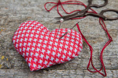 Pillow in form of heart with a needle and sewing scissors and pins on wooden background. Handmade Stock Image