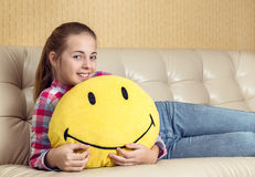 Pillow in the form of smiles in the hands of girl. Stock Images