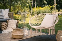 Pillow on hanging chair and basket on carpet in the garden with. Flowers. Real photo stock images