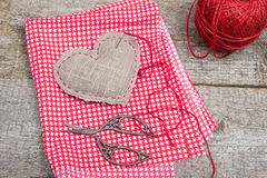 Pillow - heart of sackcloth on red checkered textile. Wooden background Stock Images
